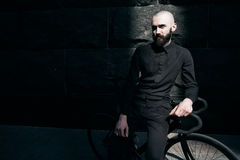 Guy with beard in black clothes sits on fix bike Royalty Free Stock Photos