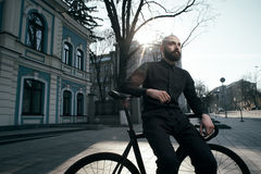 Guy with beard in black clothes sits on fix bike Royalty Free Stock Photography