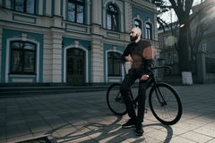 Guy with beard in black clothes sits on fix bike Stock Photo