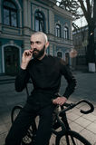 Guy with beard in black clothes sits on fix bike Stock Image