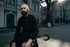 Guy with beard in black clothes sits on fix bike Royalty Free Stock Image
