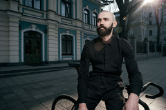 Guy with beard in black clothes sits on fix bike Stock Images