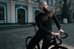 Guy with beard in black clothes sits on fix bike Stock Photos