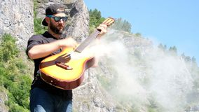 A guy with a beard in a black shirt puts on sunglasses and pretends to play an acoustic guitar from which smoke comes. Strange fun. A guy with a beard in a black stock video footage
