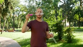 Guy with a beard blows soap bubbles. In the park a sunny day stock video footage