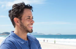 Guy with beard and blue shirt at beach looking sideways. With ocean and blue sky in the background Stock Photo