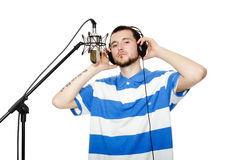 Guy with a beard in the headphones and microphone. Young guy with a beard in the headphones and microphone isolated on white background Royalty Free Stock Photos