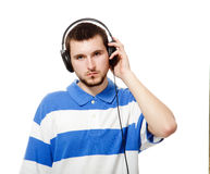 Guy with a beard, listening to music on headphones. A young guy with a beard, listening to music on headphones, isolated on a white background Stock Photos