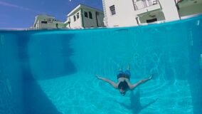 Guy with beard and long hair dives into the pool stock footage