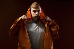 Guy with a beard and mustache dressed in a gray t-shirt and yellow jacket with a hood is standing on a brown background royalty free stock photo