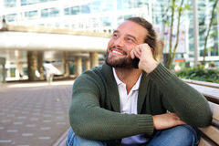 Guy with beard sitting on bench in the city with mobile phone Stock Image