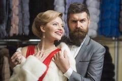 Guy with beard and woman buy furry coat. stock image