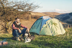 Guy bearded in jeans checkered shirt and a sleeveless jacket with a dog husk on vacation sitting on nature next to the. Guy bearded in jeans checkered shirt and Royalty Free Stock Photo
