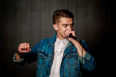 Guy Beat Boxing with Microphone. Dark Background. Royalty Free Stock Photo