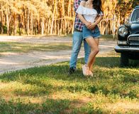 guy is behind and hugs the girl, hands together. behind is a black car. holding hands in the summer.on the hand of a guy wearing a royalty free stock photos