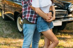 guy is behind and hugs the girl, hands together. behind is a black car. holding hands in the summer.on the hand of a guy wearing a stock photos