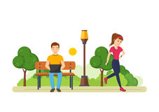 Guy behind laptop on bench in park, girl engaged athletics Royalty Free Stock Images