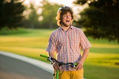 Guy with bicycle having fun outdoors. Portrait of cheerful student with bike looking aside outdoors. People and leisure concept Royalty Free Stock Image