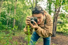 Guy biologist in glasses photographs plants. In summer forest Royalty Free Stock Images