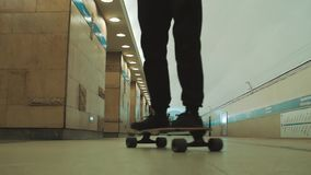 Guy rides longboard at empty underground metro station. Guy in black clothes rides longboard at empty underground metro station. Slowmotion, focus pull stock video footage