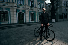 Guy in black clothes stands with bike Stock Photo