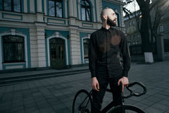 Guy in black clothes stands with fix bike Royalty Free Stock Photography