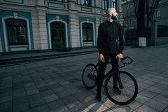 Guy in black clothes stands with fix bike Royalty Free Stock Images