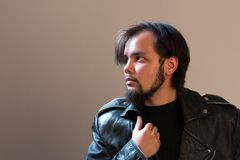 A guy in a black leather jacket with a beard looks away. Beige background. Studio shooting in the style of rock`n`roll stock image