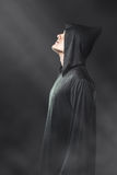 A guy in a black robe standing in the dark Stock Images