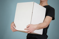 The guy in the black shirt holding a large white box. Carries a stock photography