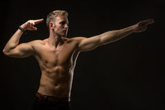 Guy in a black studio. Enviable man with a naked torso and black pants. In the studio on a black background. In a twist. It shows in side arms. Horizontal photo Royalty Free Stock Photo