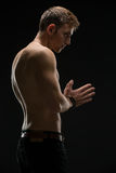 Guy in a black studio. Relief man with a naked torso and black pants. In the studio on a black background. Hands are closed in front of his hands. Vertical photo Stock Images