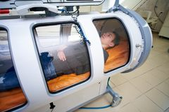 The guy in the black T-shirt lies in the hyperbaric chamber, oxygen therapy. Medical room royalty free stock photos