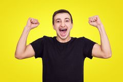 Guy in a black T-shirt rejoices victory, raises his hands up, isolate stock photos