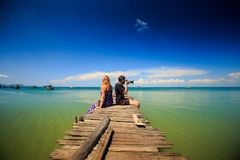 Guy Blond Girl Sit on Wooden Pier Photo Azure Sea in Tropics. Side view guy blond girl sit on wooden pier photo azure sea tropical seascape against blue sky Stock Image