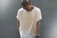 Guy with blond hair in a blank white t-shirt. Stands with his head Royalty Free Stock Image