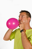 Guy blowing up a balloon Stock Images