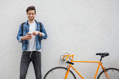 The guy in a blue denim jacket standing on wall background. young man near orange bicycle. Smiling student with bag. The guy in a blue denim jacket standing on Royalty Free Stock Photo