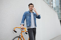 The guy in a blue denim jacket standing on wall background. young man near orange bicycle. Smiling student with bag. The guy in a blue denim jacket standing on Royalty Free Stock Images
