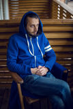 Guy in a blue jacket with hood draped on his head sitting chair Stock Photos