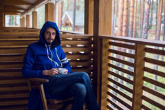 Guy in a blue jacket with  hood draped on his head sitting   chair Stock Photo