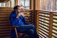 Guy in a blue jacket with hood draped on his head sitting chair Royalty Free Stock Images