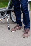 Guy in blue jeans and brown sneakers standing nearly bicycle. Guy in blue jeans and brown sneakers standing next to bicycle on the road Royalty Free Stock Photo