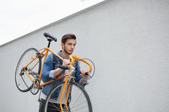 The guy in the blue jeans jacket carries on his shoulder orange bike. A young man  an  fix Royalty Free Stock Photo