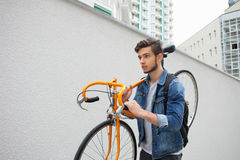 The guy in the blue jeans jacket carries on his shoulder orange bike. A young man  an  fix Stock Photo