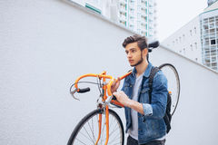 The guy in the blue jeans jacket carries on his shoulder orange bike. A young man on an orange fix bike Royalty Free Stock Images