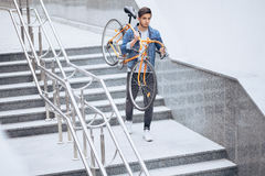 The guy in the blue jeans jacket carrying on his shoulder orange bike. Stock Photos