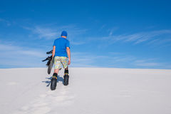 Guy in blue shirt with a snowboard climbs up the sand dune Stock Image