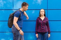 Guy in blue T-shirt and backpack on his back look at girl dressed in blue jeans and plaid shirt against blue wall stock photo