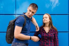 Guy in blue T-shirt and backpack on his back next to girl dressed in blue jeans and plaid shirt against blue wall royalty free stock photos